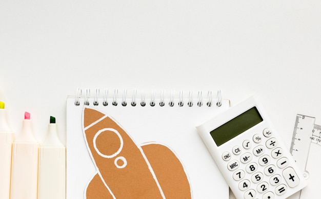 Vista superior de lo esencial para el regreso a la escuela con un cuaderno y una calculadora