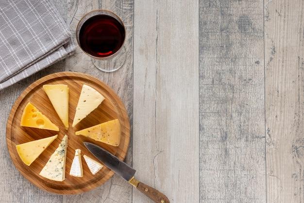 Vista superior lonchas de queso y una copa de vino