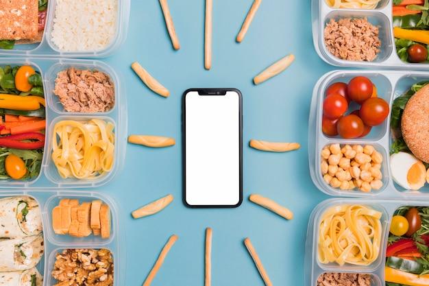 Vista superior de loncheras con teléfono en blanco y palitos de pan
