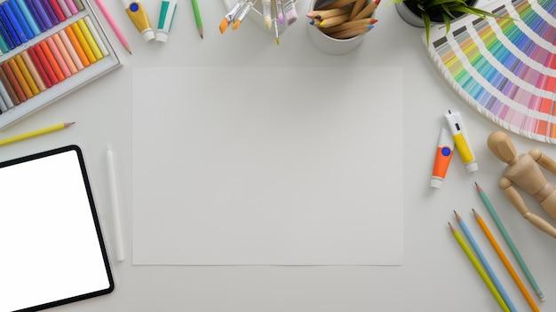 Vista superior del lugar de trabajo del diseñador con tableta digital, papel para bocetos y suministros de diseño