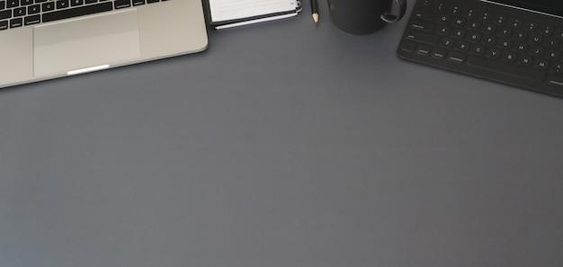Vista superior del lugar de trabajo moderno con computadora portátil y suministros de oficina en mesa gris oscuro