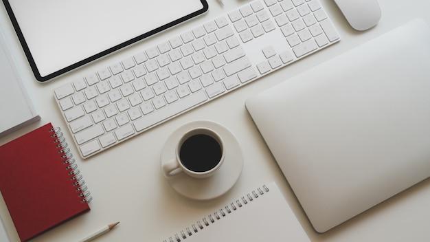 Vista superior del lugar de trabajo moderno con computadora portátil, taza de café y otros accesorios de oficina