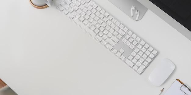Vista superior del lugar de trabajo moderno con computadora de teclado y suministros de oficina en el fondo de la tabla blanca