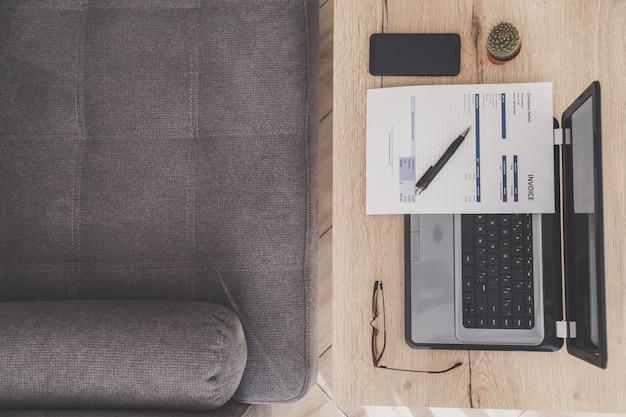 Vista superior del lugar de trabajo de la oficina en casa. portátil, factura y anteojos en mesa de madera, sofá