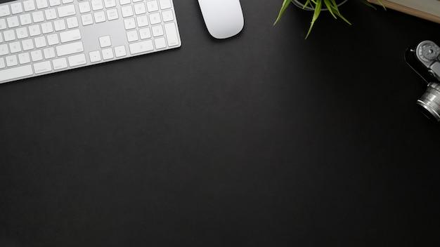 Vista superior del lugar de trabajo con teclado de computadora, espacio de copia y cámara en mesa negra
