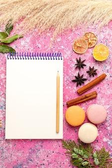 Vista superior de macarons franceses con bloc de notas en superficie rosa