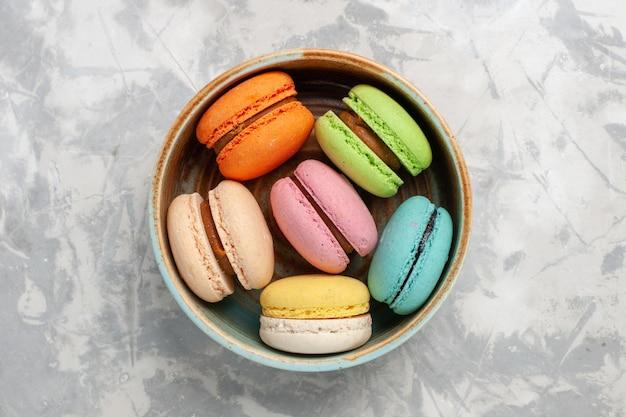 Vista superior macarons franceses coloreados deliciosos pasteles en superficie blanca