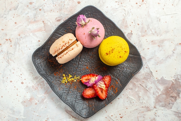 Vista superior macarons franceses dentro de la placa en la mesa blanca galleta galleta pastel dulce