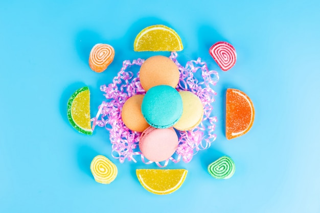 Una vista superior de macarons franceses junto con mermeladas de colores sobre el fondo azul confitura confitería pastel de azúcar