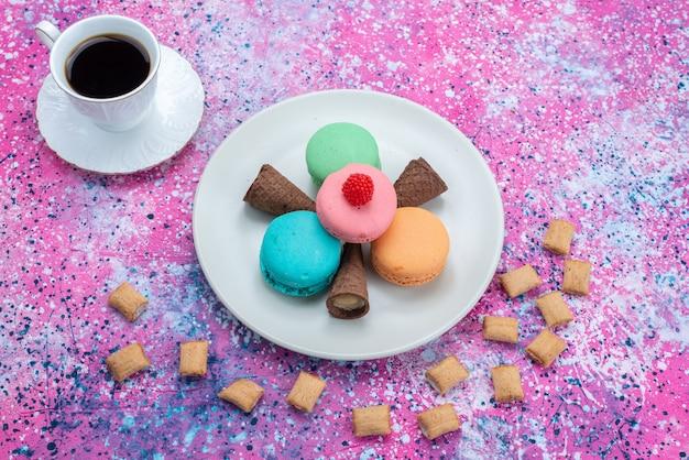 Vista superior de macarons franceses junto con una taza de café caliente en el fondo de color pastel de color dulce de azúcar