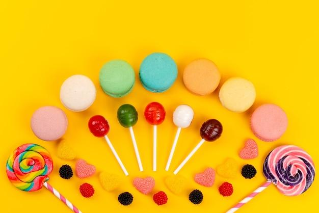 Una vista superior de macarons franceses redondos forrados de colores junto con piruletas y mermeladas en amarillo, pastel de azúcar dulce