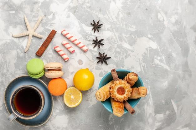 Vista superior de macarons franceses con taza de bagels de té en superficie blanca