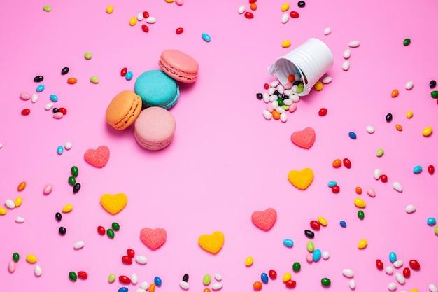 Una vista superior de macarons y mermelada de coloridos pasteles franceses junto con caramelos multicolores sobre el fondo rosa caramelo dulce
