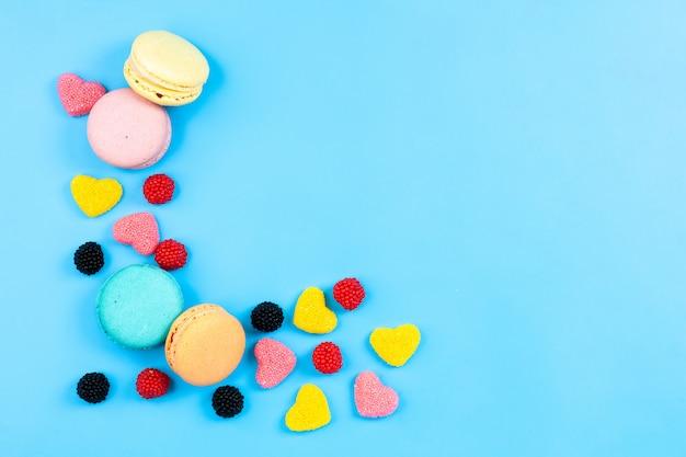 Una vista superior macarons y mermeladas coloridos pasteles franceses y caramelos aislados en el fondo de color azul pastel dulce de azúcar