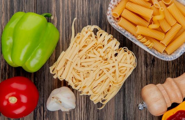 Vista superior de macarrones como tagliatelle ziti con sal de tomate ajo pimienta en madera