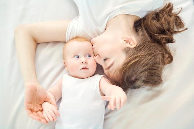 Vista superior de una madre feliz besando a un bebé acostado en una cama en el interior.
