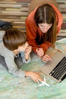 Vista superior de la madre y el niño en casa con una computadora portátil en busca de un lugar para viajar