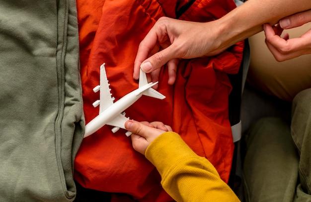 Vista superior de la madre y el niño poniendo figurilla de avión en el equipaje
