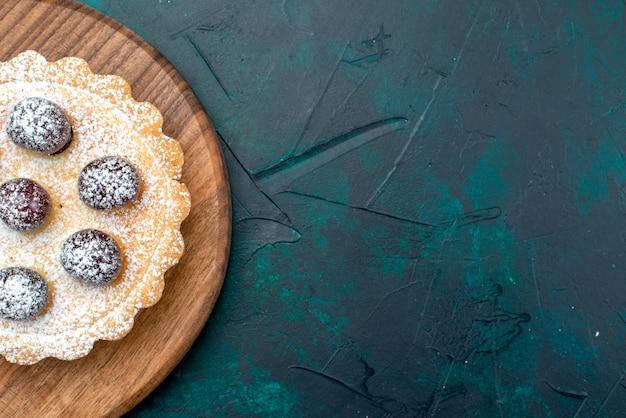 Vista superior de la magdalena con azúcar en polvo y deliciosas cerezas en la mesa