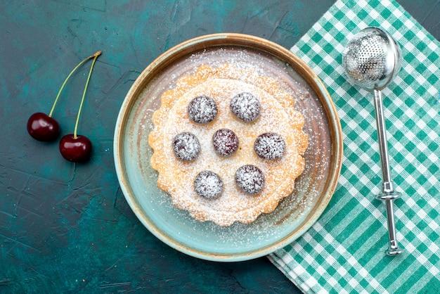 Vista superior de la magdalena con azúcar en polvo junto al racimo de cerezas