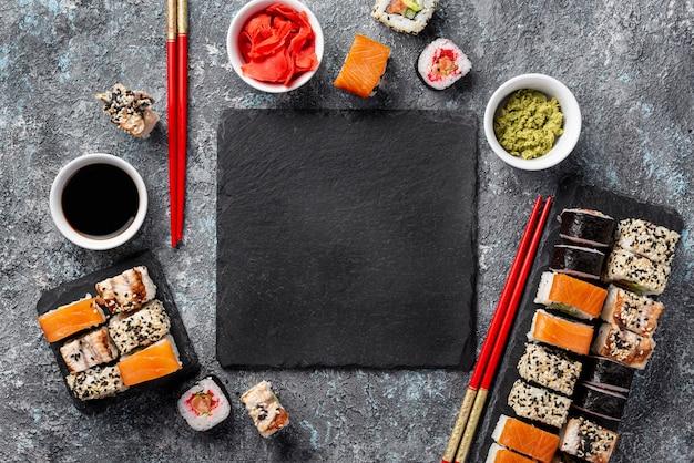 Vista superior maki sushi rolls palillos y salsa de soja con pizarra en blanco