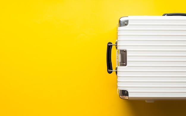 Vista superior de maletas blancas sobre fondo de color.tiempo de viaje y vacaciones.