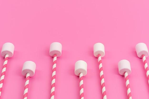 Una vista superior de malvaviscos blancos con palos de color rosa en el escritorio rosa, color dulce de azúcar