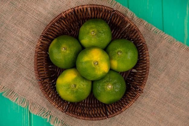 Vista superior de mandarinas en canasta en servilleta beige en pared verde