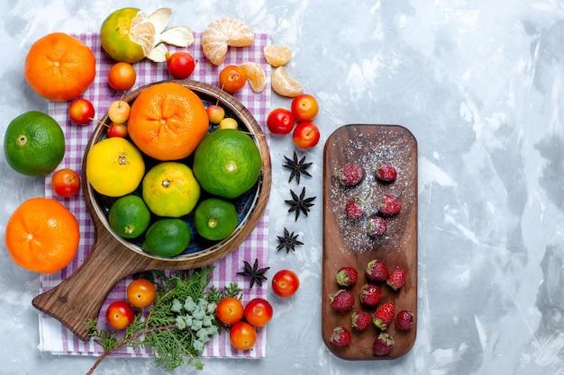 Vista superior de mandarinas frescas agrias con limones y ciruelas sobre superficie blanca clara