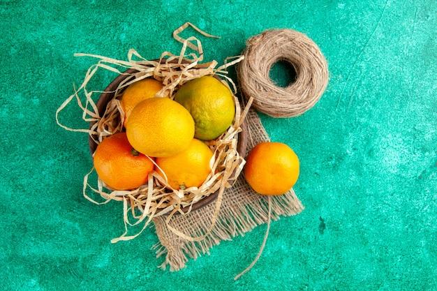 Vista superior mandarinas frescas agrias sobre fondo verde