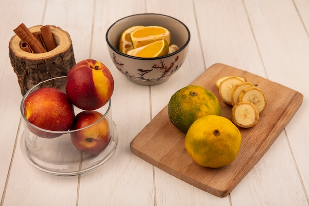 Vista superior de mandarinas frescas en una tabla de cocina de madera con rodajas de plátano con melocotones en un recipiente de vidrio sobre una superficie de madera blanca