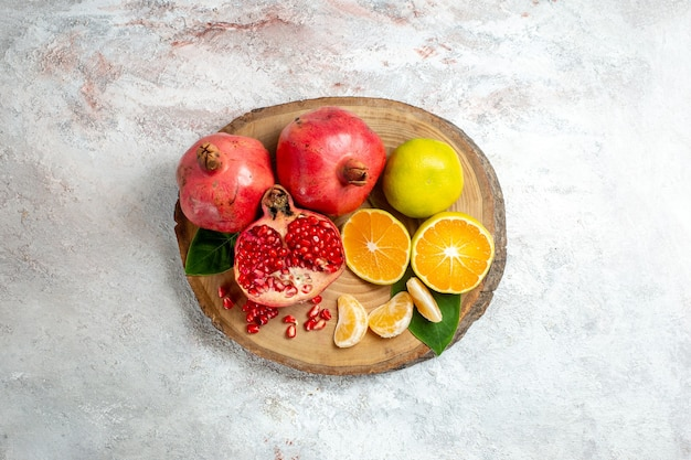 Vista superior de mandarinas y granadas frutas frescas suaves sobre fondo blanco árboles frutales color salud fresca