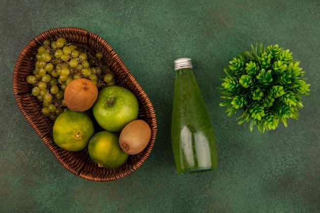 Vista superior de mandarinas verdes con kiwi de manzana y uvas en una canasta con una botella de jugo en una pared verde
