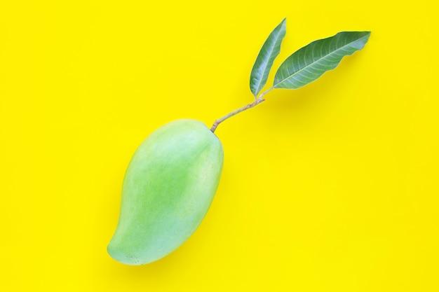 Vista superior de mango verde fresco, frutas tropicales sobre fondo amarillo.