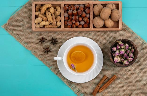 Vista superior de maní con avellanas nueces y una taza de té con canela sobre un fondo azul claro