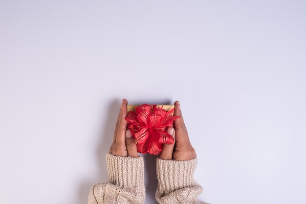 Vista superior de la mano con caja de regalo en el espacio de trabajo