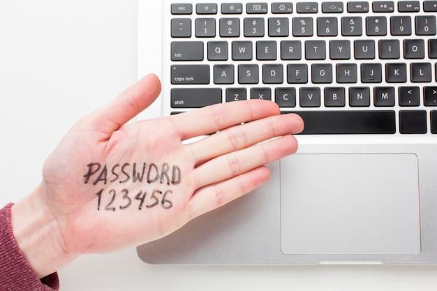 Vista superior de la mano con la contraseña escrita y la computadora portátil
