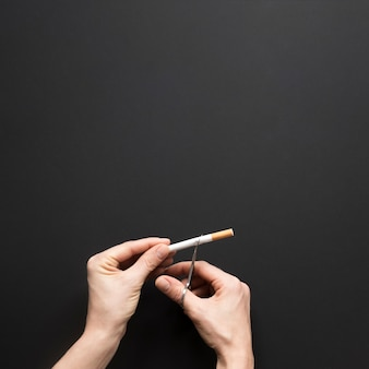 Vista superior mano cortando cigarro