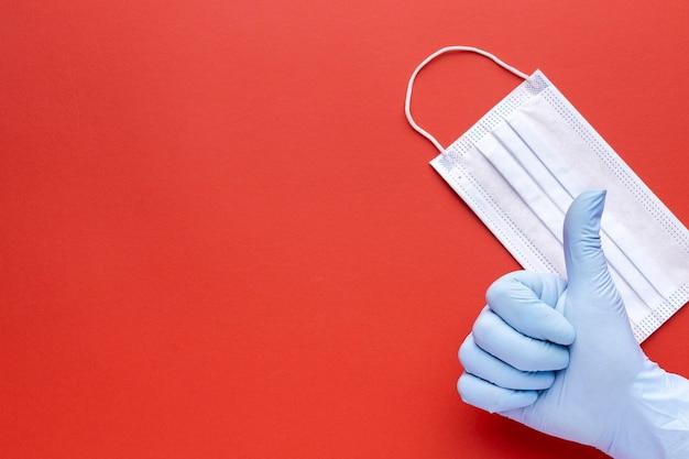 Vista superior de la mano dando pulgares hacia arriba con máscara médica y espacio de copia