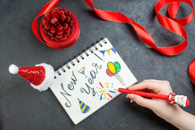 Vista superior de la mano escribiendo un cono de conífera con cinta roja y cuaderno con escritura de año nuevo y sombrero de santa claus sobre fondo oscuro