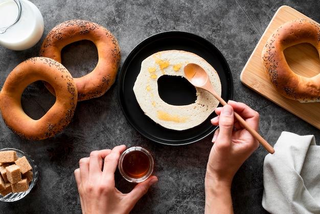 Vista superior mano esparcir miel en bagel en rodajas