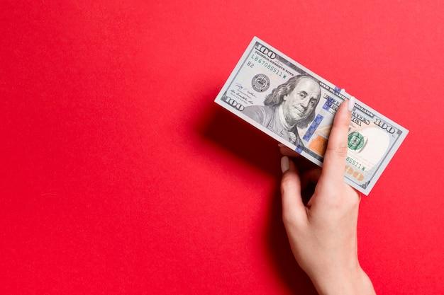 Vista superior de la mano femenina dando billetes de cien dólares en colores de fondo