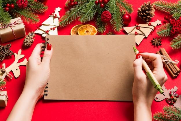 Vista superior de la mano femenina haciendo algunas notas en noteebok en rojo. decoraciones de año nuevo y juguetes.