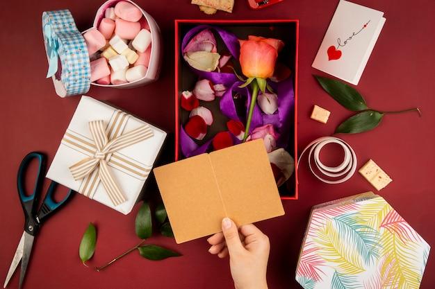 Vista superior de la mano femenina con una pequeña postal abierta sobre la caja de regalo con flor color de rosa color coral con pétalos dispersos y una caja llena de malvaviscos en la mesa roja