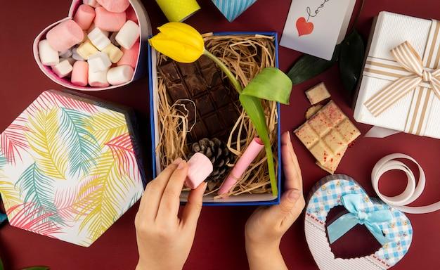 Vista superior de la mano femenina poniendo malvavisco en una caja de regalo con flor de tulipán de color amarillo, barra de chocolate oscuro, cono y paja en la mesa de color rojo oscuro con una caja llena de malvavisco