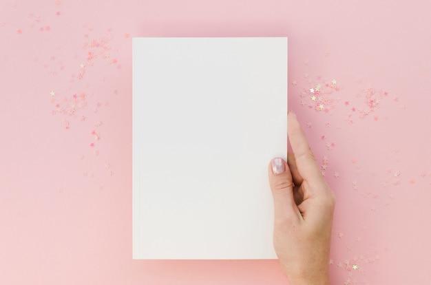 Vista superior de la mano femenina que sostiene el cuaderno