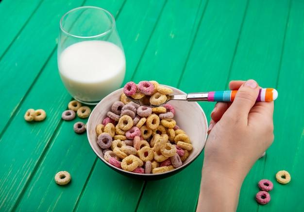Vista superior de la mano femenina sosteniendo una cuchara con cereales en un tazón con un vaso de mil en verde