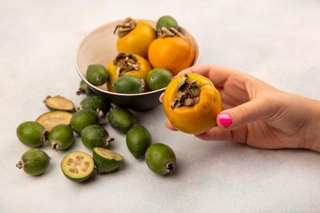 Vista superior de la mano femenina sosteniendo una fruta de caqui maduro naranja con feijoas y caquis aislado sobre una superficie gris