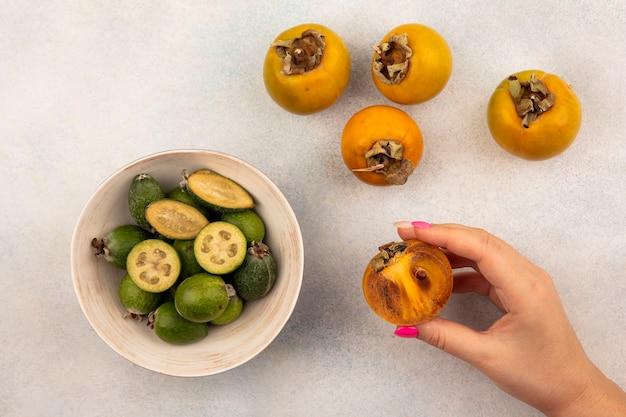 Vista superior de la mano femenina sosteniendo una fruta de medio caqui maduro con feijoas en un cuenco y caquis aislado sobre una superficie gris