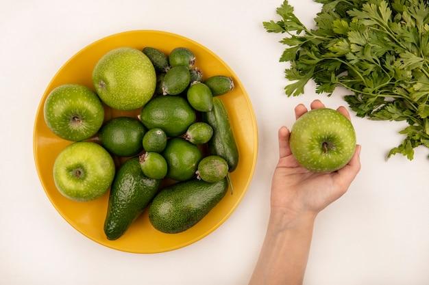 Vista superior de la mano femenina sosteniendo una manzana con plato amarillo de frutas frescas como manzanas, feijoas y aguacate sobre una superficie blanca